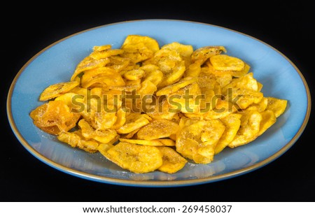 Cuban Cuisine: delicious green plantain salty chips or fries served for snack in a blue plate. Green plantain chips or fries are part of the Cuban traditional and creole cuisine