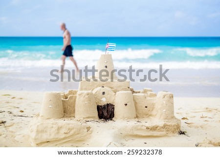 Cuban Sandcastle with the country Flag on one of the most Beautiful Beach of Cuba with a tourist in background - stock photo