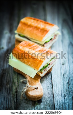 Cuban sandwiches on wooden background - stock photo