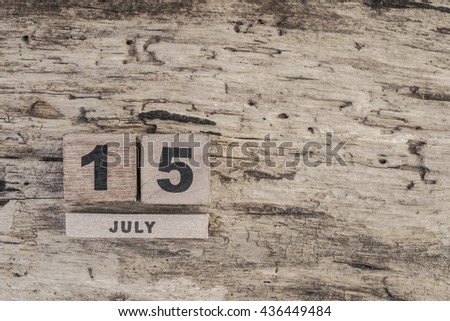 cube calendar for july on wooden background with copy space - stock photo