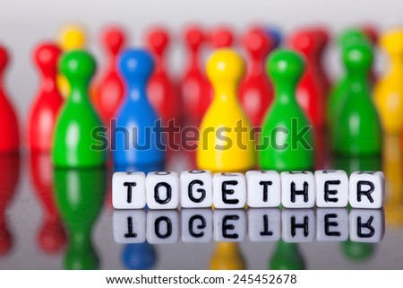 Cube Letters show together  in front of unsharp ludo figures.Laying on a mirror plate. - stock photo