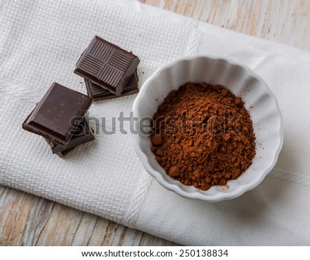 Cube of chocolate and a bowl of cocoa - stock photo