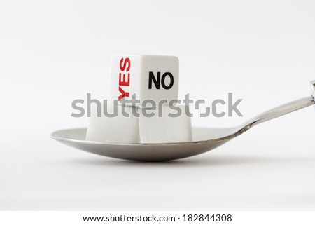 Cube sugar on a spoon with yes or no dice - stock photo