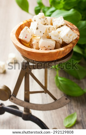Cubed feta cheese in olive wood bowl on old rustic scales with basil. Selective focus. - stock photo
