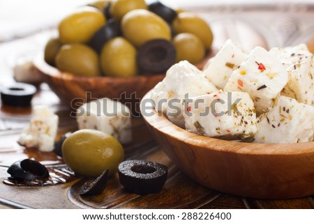 Cubed feta cheese with olives in olive wood bowl and green and black olives on rustic wooden background.  Selective focus. - stock photo