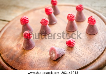 Cuberdons with fresh raspberries on the wooden board