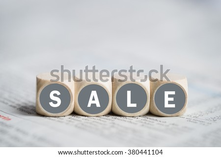 cubes forming the word sale on a newspaper - stock photo