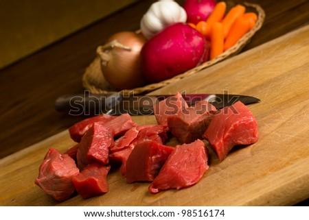 Cubes of beef and garden vegetables for stew preparation - stock photo