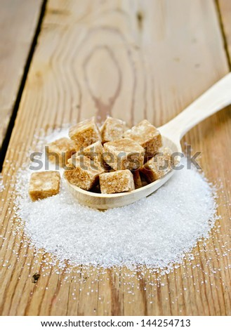 Cubes of brown sugar in a wooden spoon and a white granulated sugar on a wood table