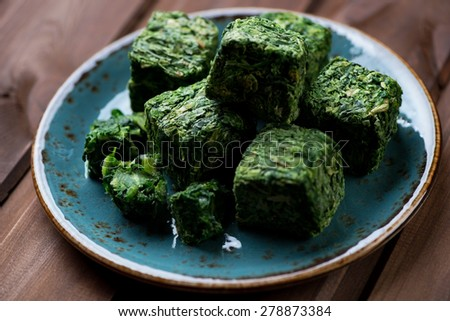 Cubes of chopped and then compressed spinach, selective focus - stock photo