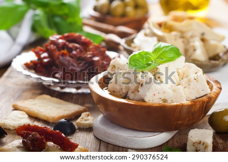 Cubes of feta cheese in olive wood bowl and sun dried tomatoes on rustic wooden background.  Selective focus. - stock photo