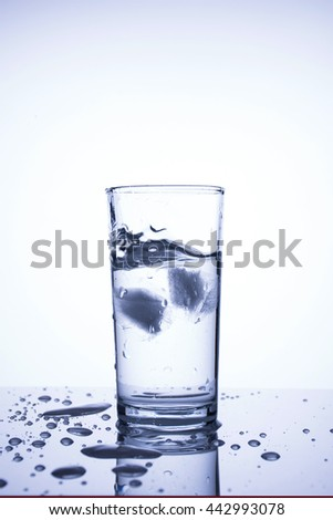 Cubes of natural ice splashing into glass of  clean water, vertical image, front view, room for text