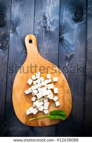 Cubes of raw tofu and fresh spinach on shabby cutting board. Top view - stock photo