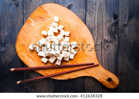 Cubes of raw tofu and two chopsticks on shabby cutting board - stock photo