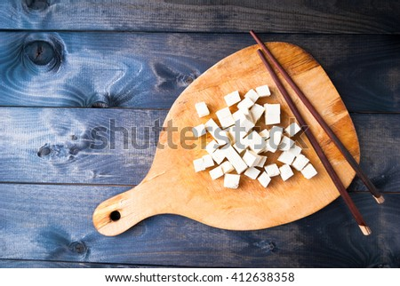 Cubes of raw tofu and two chopsticks on shabby cutting board. Copy space - stock photo