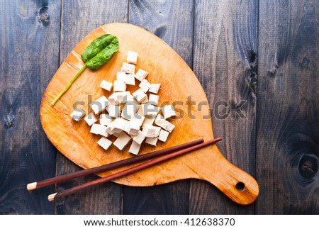Cubes of raw tofu, fresh spinach and chopsticks on rustic cutting board - stock photo
