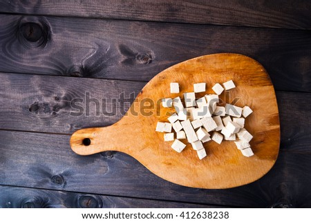 Cubes of raw tofu on shabby wooden cutting board - stock photo