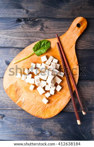 Cubes of raw tofu, spinach and chopsticks on shabby cutting board - stock photo