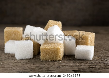 Cubes of sugar cane brown and white refined over rustic wooden background - stock photo