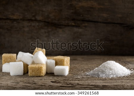 Cubes of sugar cane brown and white refined over wooden background - stock photo