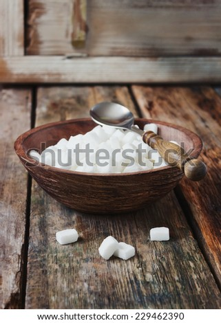 cubes of white sugar in a wooden bowl and spoon on old wooden table. - stock photo