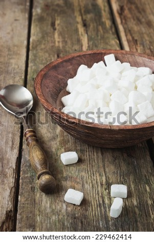 cubes of white sugar in a wooden bowl on old wooden table. - stock photo