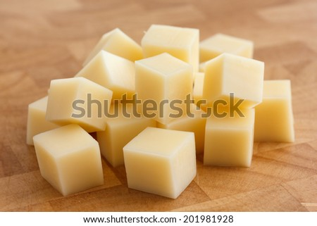 Cubes of yellow cheese stacked randomly on wood chopping board. - stock photo