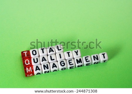 cubes with text ,TQM Total Quality Management  on green background - stock photo