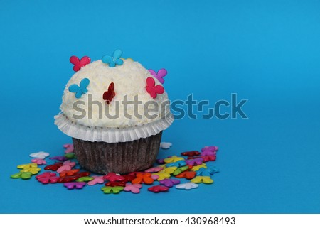 cuccake on blue background with littel butterflies