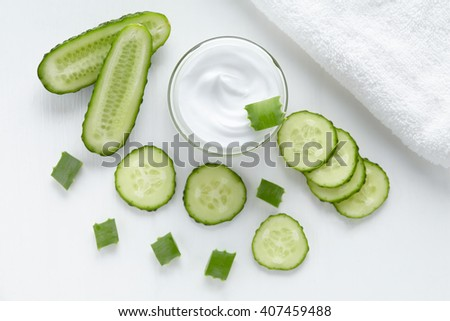Cucumber and aloe cosmetic cream face, skin and body care hygiene moisture lotion wellness therapy mask in glass jar with towel on white background - stock photo