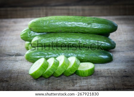 Cucumber and slices on wooden background - stock photo