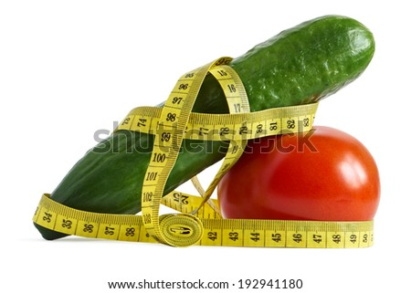 Cucumber and tomato with measuring tape over white  - the concept of dieting and health