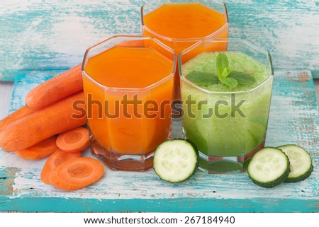 Cucumber, carrot Juices and vegetables on white wooden table - stock photo