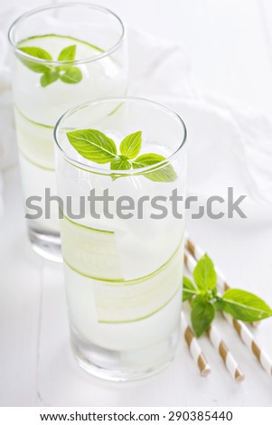 Cucumber cooler in tall glasses garnished with basil - stock photo