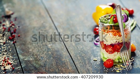 Cucumber, quinoa, tomato, onion, carrot and mint salad in a jar  on rustic wooden table - stock photo