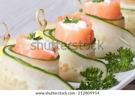 cucumber rolls with salmon, cream cheese and herbs on a white plate macro horizontal   - stock photo