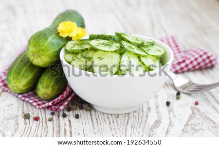 cucumber salad garnished with dill in white bowl