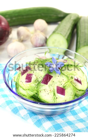 Cucumber salad with onions, dill and borage flower on a light background - stock photo