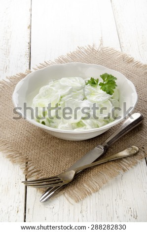 cucumber salad with sour cream and parsley in a bowl
