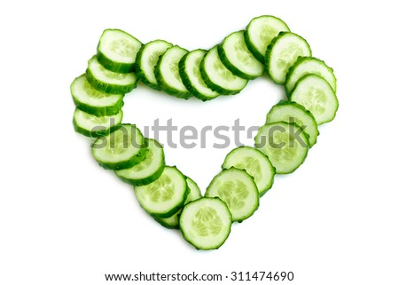 Cucumber slices arranged as heart shape isolated over white background - stock photo