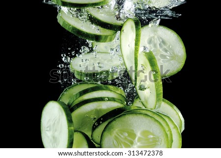 Cucumber slices falling into water at black background - stock photo