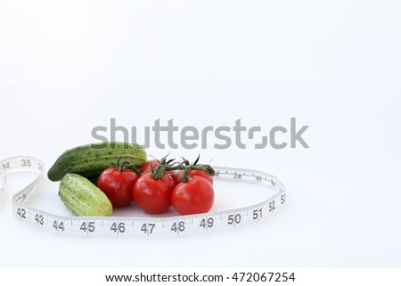 Cucumbers, cherry tomatoes and tape measure on a white background.