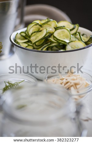 Cucumbers in a bowl, sliced to be pickled.