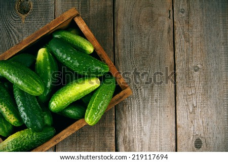 Cucumbers in a box on a wooden background. - stock photo