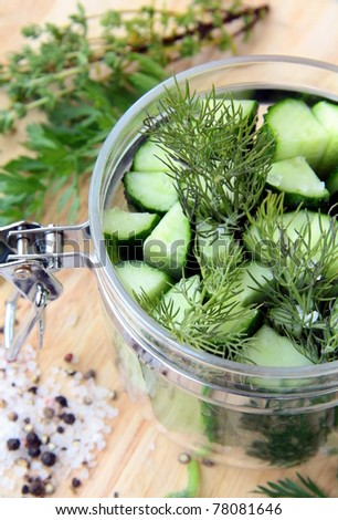 cucumbers in the jar with dill salt and pepper on the table - stock photo