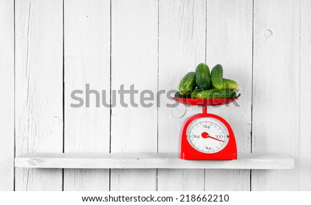 Cucumbers on scales on a wooden shelf. - stock photo