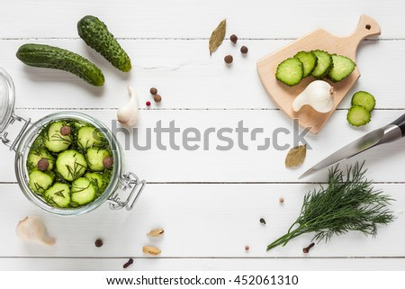 Cucumbers ready for pickling and ingredients on white table with copy space. Homemade vegetable canning. Flat lay, top view. - stock photo