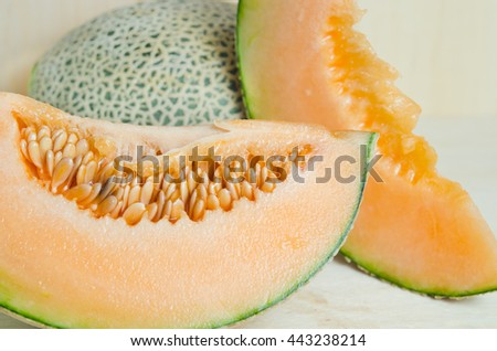 Cucumis melo or melon with half and seeds on wooden plate (Other names are Melon, cantelope, cantaloup, honeydew, Crenshaw, casaba,  Persian melon, and Santa Claus or Christmas melon) - stock photo