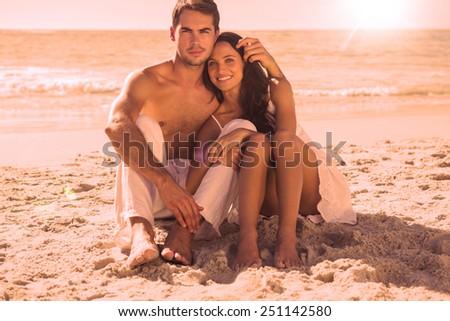 Cuddling couple smiling at camera at the beach - stock photo