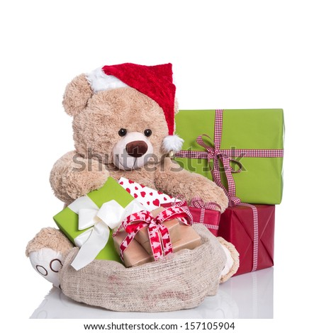 Cuddly teddy bear wearing Christmas hat and gift boxes on white background